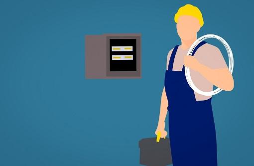 Kék overálos villanyszerelő szakember rajza elosztó szekrény előtt.